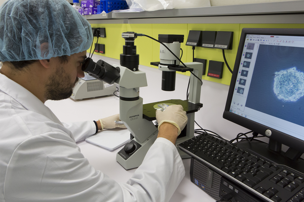 Científico mirando a través de microscopio