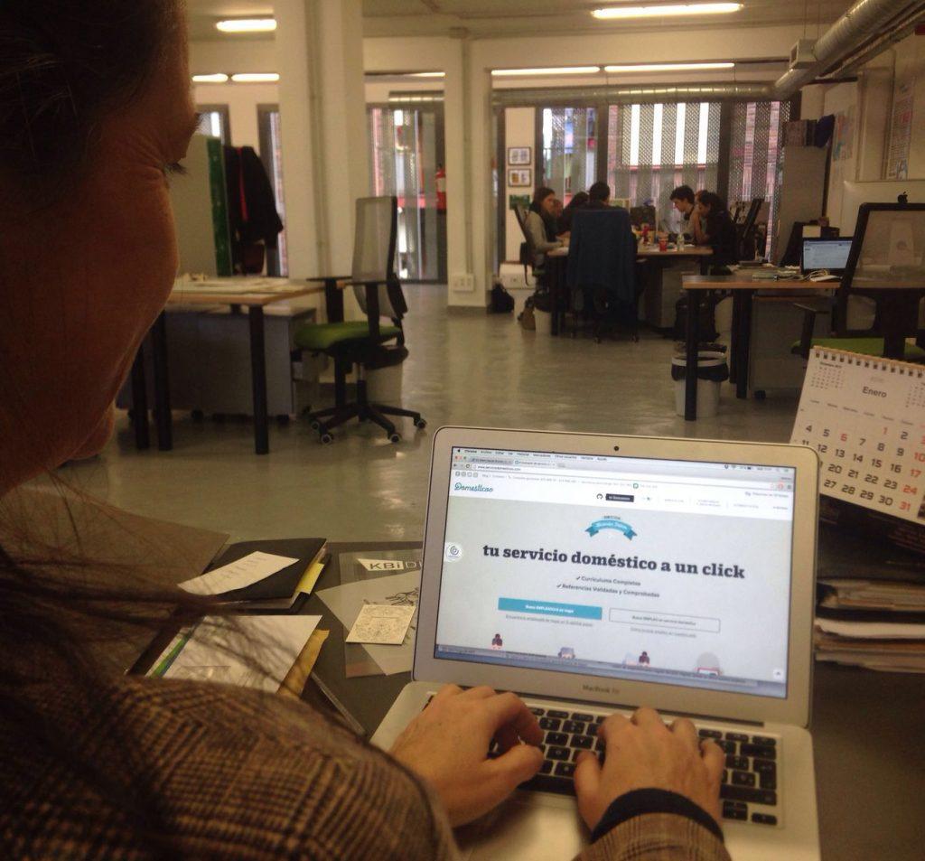 En una oficina una mujer visita una web en un ordenador, al fondo una mesa con gente reunida