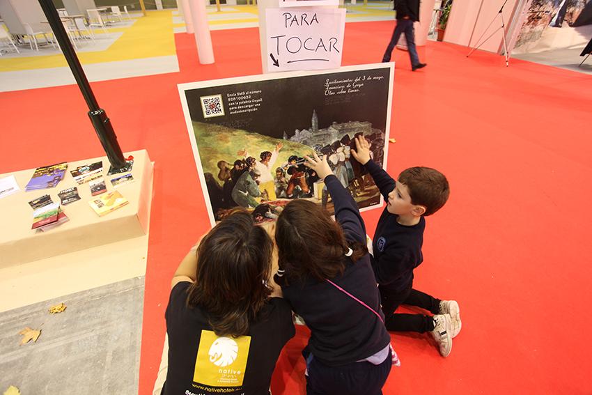 Monitora y dos niños tocando un cuadro de Goya