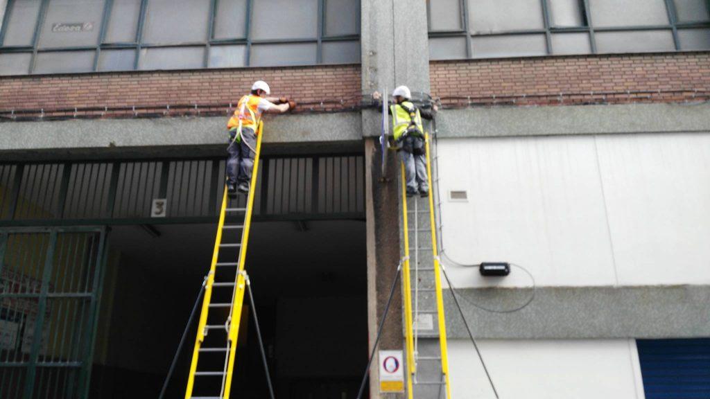 Dos operarios subidos en una escalera larga cada uno y arreglado unos cables