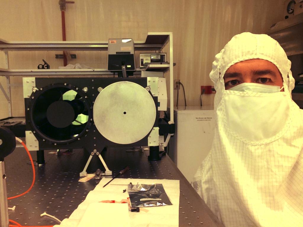 Científico con ropa de protección junto a máquina